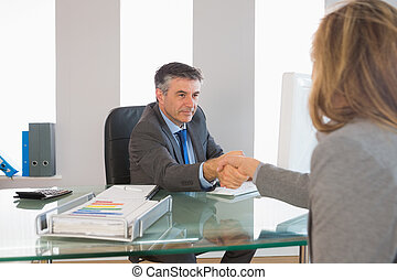 Serious businessman shaking the hand of a interviewee