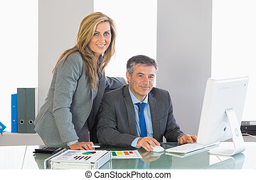 Two satisfied businesspeople looking at camera using a computer