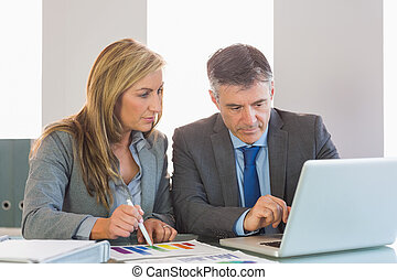 Attentive mature businessman showing something on computer to an attentive blonde businesswoman at office