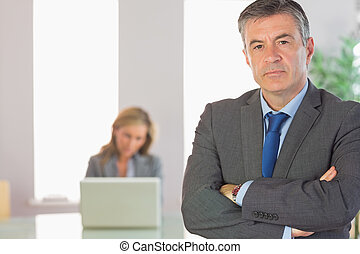 Unsmiling mature businessman looking at camera crossed arms...