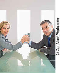 Two smiling mature businesspeople having a showdown sitting around a table at office