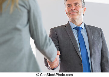 Happy businessman shaking a hand - Happy mature businessman...