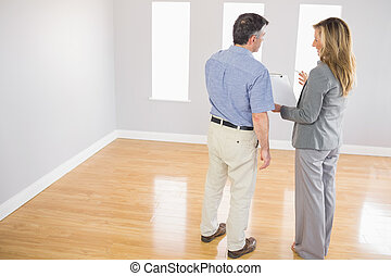 Blonde realtor showing an empty room and some documents to a...