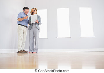 Cheerful blonde realtor showing an empty room and some...