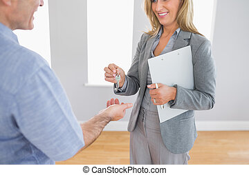 Close up of a smiling blonde realtor delivering a key to a...