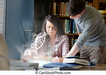 Concentrated college students analysing dna on digital...