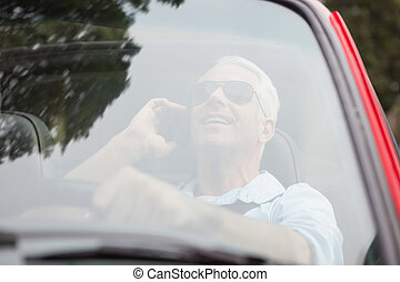 Smiling handsome man in red convertible having phone call...