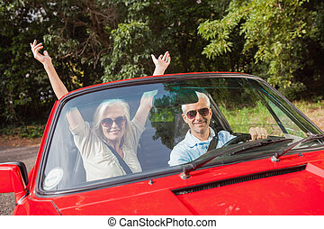 Mature couple in red cabriolet cheering at camera - Mature...