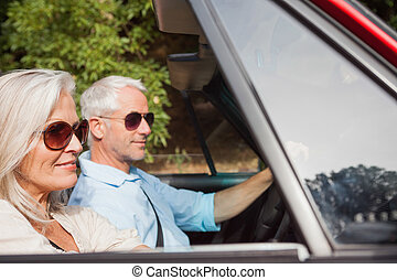 Side view of mature couple driving red cabriolet on sunny...