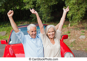 Cheerful mature couple posing by their red convertible on...