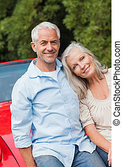 Cheerful mature couple sitting on their red convertible on...