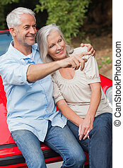 Smiling mature couple sitting on their red convertible on...
