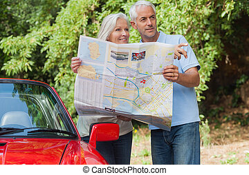 Smiling mature couple reading map looking for direction -...
