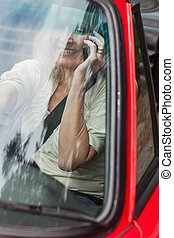 Smiling mature woman on the phone driving red cabriolet on...