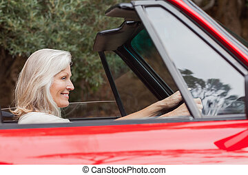 Happy mature woman driving red convertible on sunny day