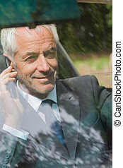 Cheerful businessman on the phone driving expensive car