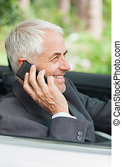 Cheerful mature businessman on the phone driving expensive...