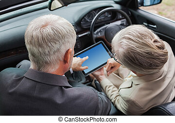Mature partners working together on tablet in classy car on...