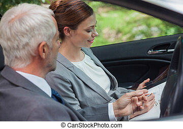 Partners working together in classy car on a bright day