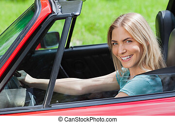 Cheerful woman driving red cabriolet on a sunny day