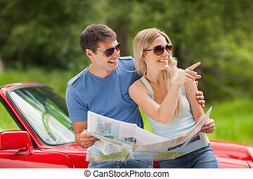 Cheerful young couple reading map - Cheerful young couple on...