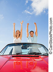 Cheerful couple standing in red cabriolet on a sunny day