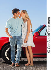 Cute couple kissing against their red cabriolet on a sunny...