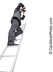Low angle view of businessman standing on ladder using...