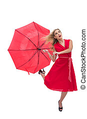 Beautiful woman wearing red dress holding umbrella against...