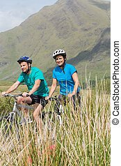 Fit couple cycling together through mountain terrain