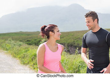 Athletic couple taking a break from jogging in the...