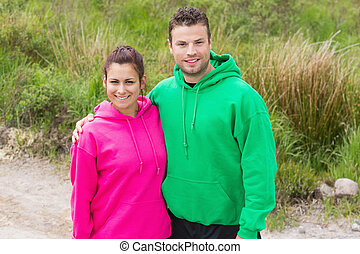 Fit couple looking at camera and embracing on a country...