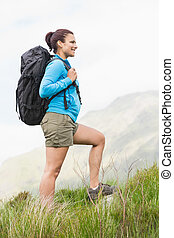 Attractive hiker with backpack walking uphill in the...