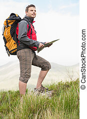 Handsome hiker with rucksack walking uphill holding a map in...