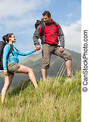 Handsome hiker helping his girlfriend uphill in the...