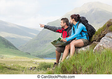Couple taking a break after hiking uphill and holding map in...