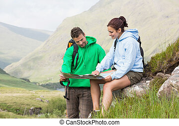 Couple resting after hiking uphill and looking at map in the...