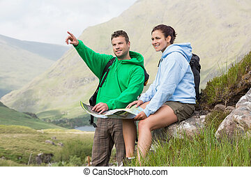 Couple resting after hiking uphill and consulting map in the...