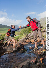 Man helping his pretty girlfriend to cross a river on a hike...
