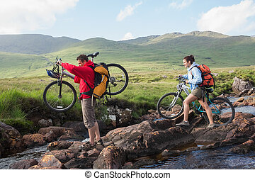Couple crossing a stream holding their bikes in the...