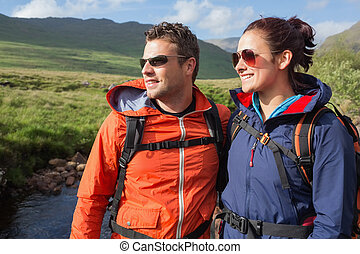 Couple wearing rain jackets and sunglasses admiring the...