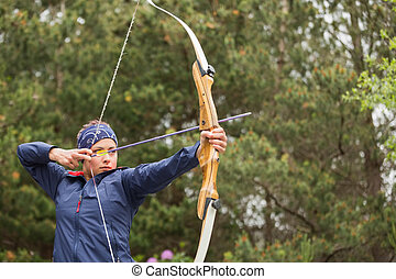 Concentrated brunette practicing archery at the range