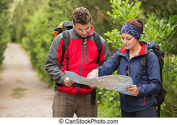 Happy couple going on a hike together looking at map in the...