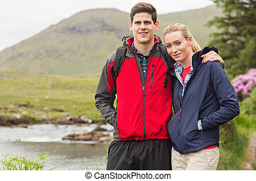 Fit couple on a hike smiling at camera in the countryside