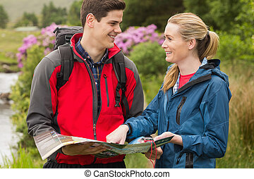Happy couple reading map on a hike in the countryside