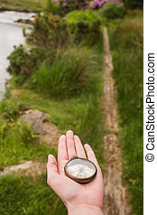 Hand holding old fashioned compass showing the way on a...