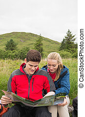 Cheerful couple taking a break on a hike to look at map in...