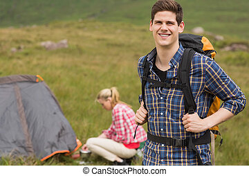 Cheerful man carrying backpack while girlfriend is pitching...