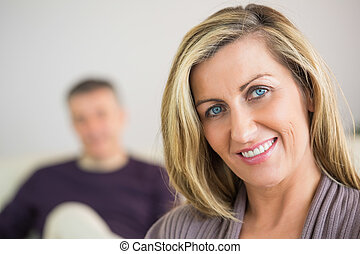 Smiling woman with her husband in the background - Smiling...