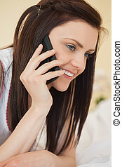 Smiling girl calling someone with a mobile phone lying on a bed